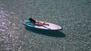 Pretty girl relaxing in the sea on a SUP board