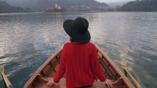 Stylish woman enjoying nature in a wooden boat