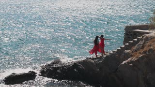 Twin sisters on standing on cliff near the sea