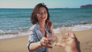Two girls cheers with wine glasses in a beach