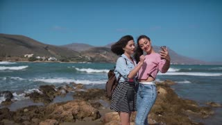 Two girls making selfie on the cliff over the sea
