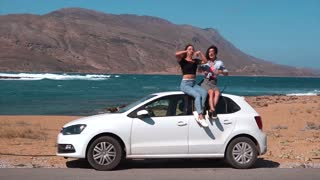 Two girls sitting on a car at the beach