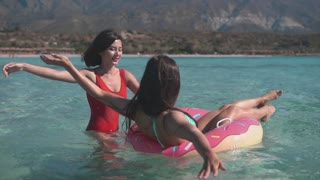 Two happy ladies on inflatable ring