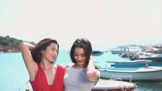 Two happy women dancing in red dresses