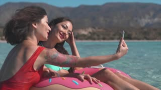 Two young girls on inflatable ring making selfie