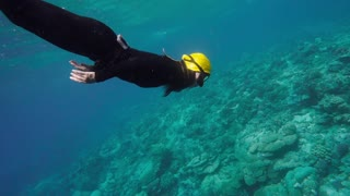 Woman in black suit free diving On a coral reef