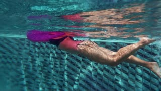 Woman swims with lifebuoy in the swimmimg pool