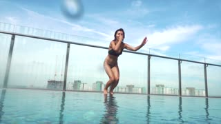 Young Woman jumping in swimming pool, slow motion