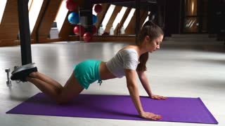 woman doing push ups in the gym with a ball