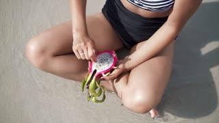 Woman eating Dragon Fruit on the beach