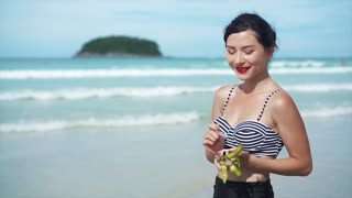 woman eating dragon fruit with a spoon on a beach