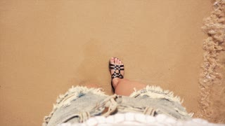 Woman feet on sea beach sand
