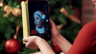 woman in red santa hat taking selfie picture