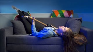 woman on the sofa and playing guitar