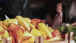 Woman picking up peppers in market