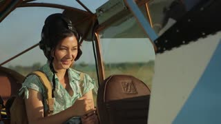 woman pilot in old airplane at sunset