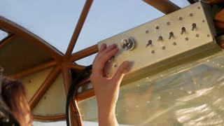 woman pilot's hands on tool panel in plane