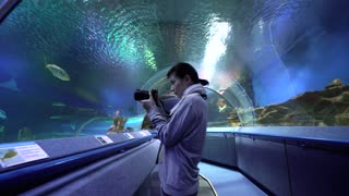 Woman taking pictures of coral fish in oceanarium