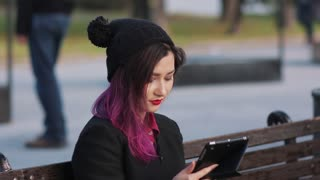 Woman using tablet pc in the park