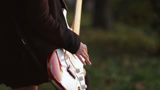 Woman with guitar playing hard-rock outside