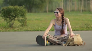young girl smiling posing with skateboard