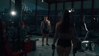Young man and woman flexing muscles on gym machine