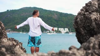 Young man standing on a rock with raised hands