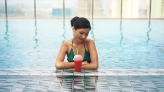 young sexy girl drinking cocktail in pool
