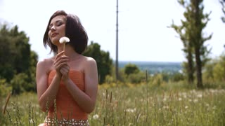 Young spring fashion woman blowing dandelion