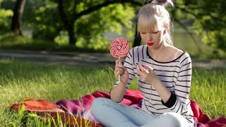 Young woman with lollipop and music player