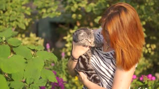 Young woman with scottish-fold cat outside