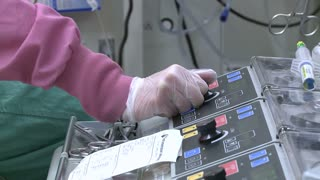 Doctor's hand on heart bypass machine