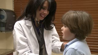 Female nurse checks child's breathing (2 of 5)