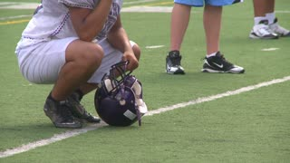 Football player squatting on sidelines