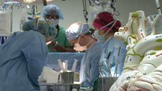 Model of heart with surgical team in background (2 of 4)