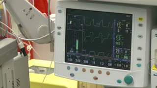 Vitals monitor with cell-saver machine in background