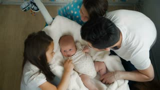 A family of newborn baby girl sister and the parents.