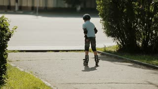a little boy learning to roller skate