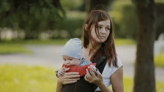 A young mother carrying her baby in a baby carrier in park