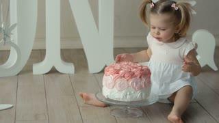 baby biting a birthday cake