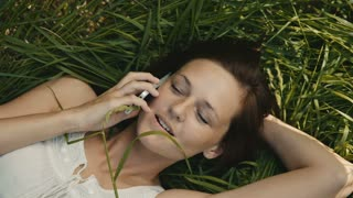 beautiful woman lying on the grass talking on the phone and smiling