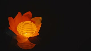 glowing paper lantern a flower shape floats on water