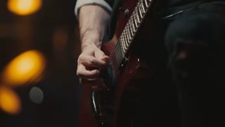 guitarist plays on a red electric guitar at a rock concert