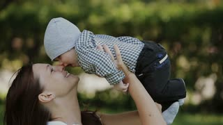 Happy baby boy playing with mother in the summer park