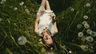 portrait of Pretty girl blowing on a dandelion lying on sunny meadow