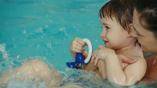 close up of mother with her baby have fun in the pool