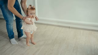 Dad teaches his little daughter to walk. Baby's first steps