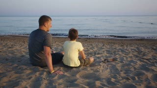 father and son talking on the sea coast