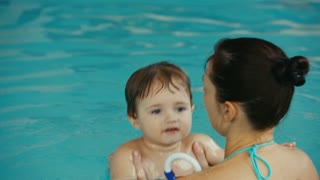 funny baby plays with his mother in the pool