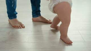 Legs of mother and baby. First steps